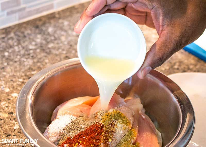 Pouring citrus juice on chicken