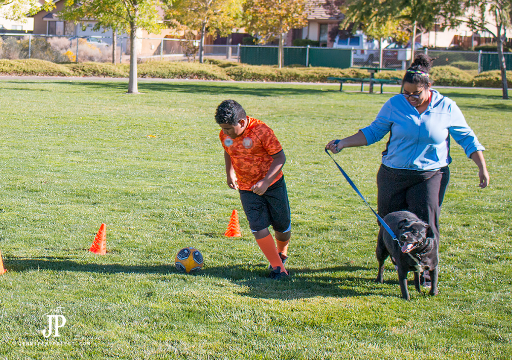 run-with-dog-as-family-playing-soccer-jenniferppriest