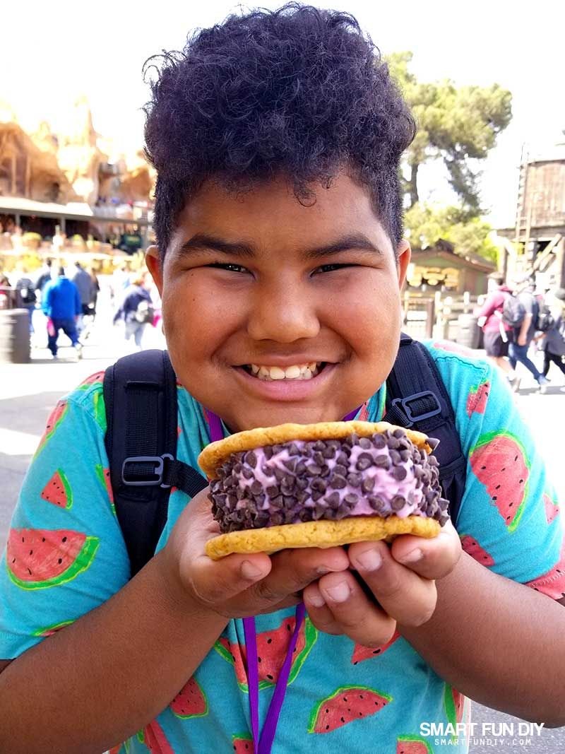 Boy with boysenberry ice cream cookie sandwich