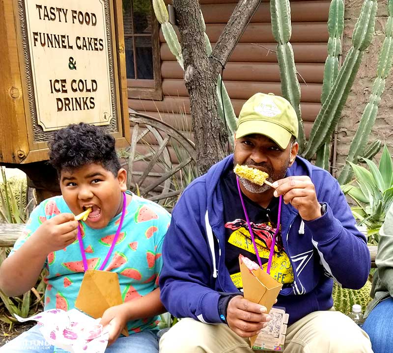 Family eating fries and elote from Knott's Berry Farm Boysenberry Festival