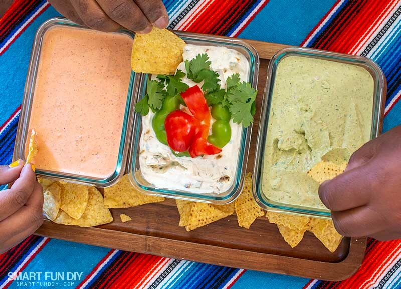 Family dipping tortilla chips into trip of Mexican Dip Recipes made to look like Mexican flag