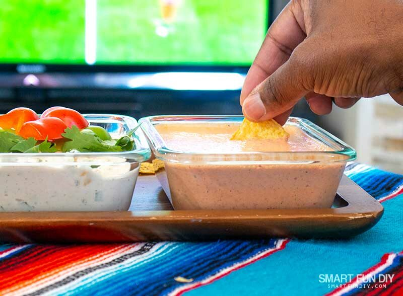 Man dipping tortilla chip into red pepper dip while watching soccer game on TV