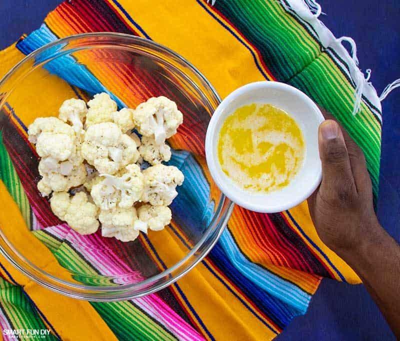 Adding butter to cauliflower florets for spicy cauliflower recipe