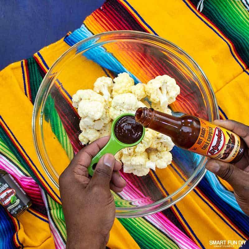 Adding El Yucateco Chile Chipotle hot sauce to cauliflower florets for spicy cauliflower recipe
