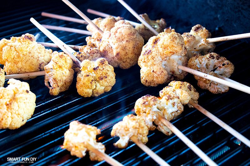 Cauliflower lollipops on hot grill with smoke rising