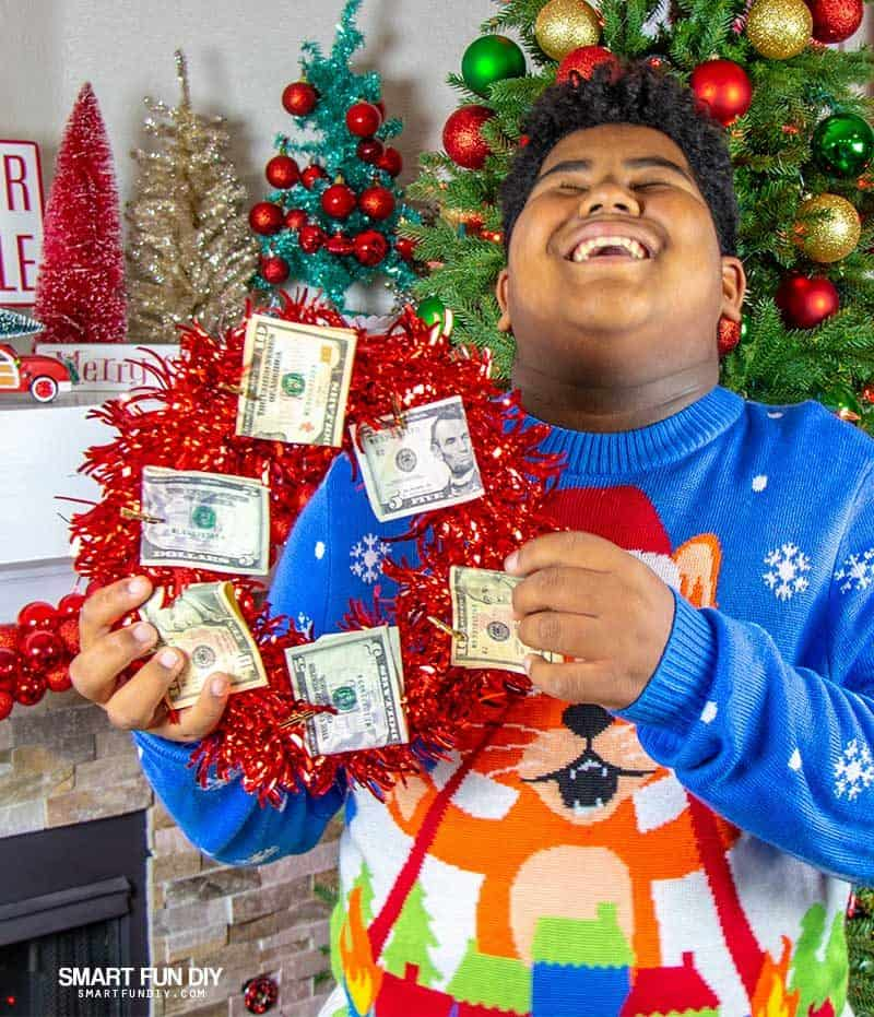 boy laughing holding wreath with money on it