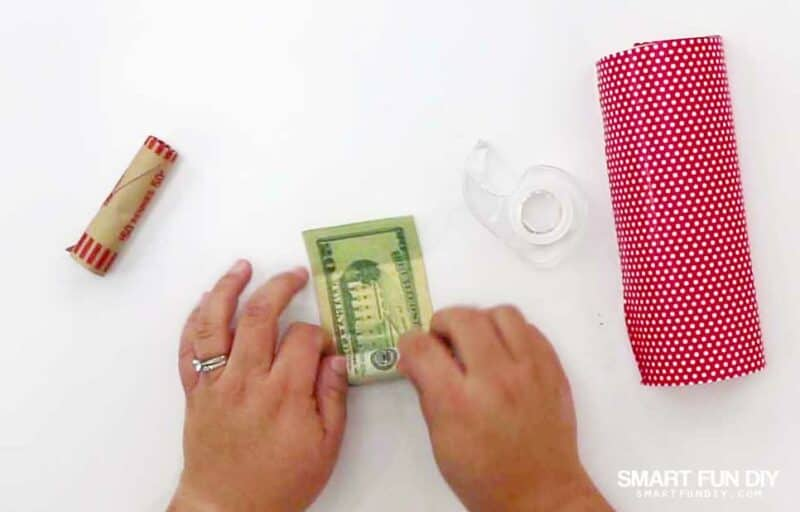 rolling cash around roll of dimes to put inside empty roll of pennies