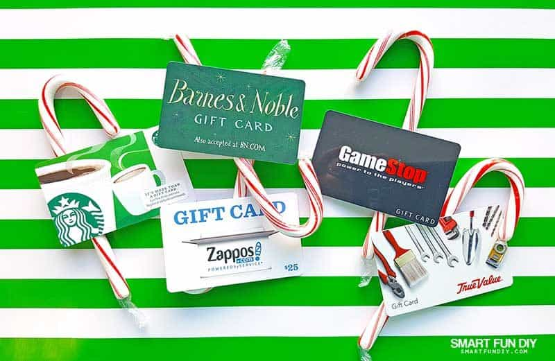 gift cards and candy canes on green striped wrapping paper