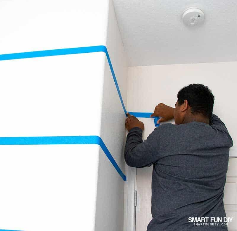 boy applying masking tape to walls to paint stripes