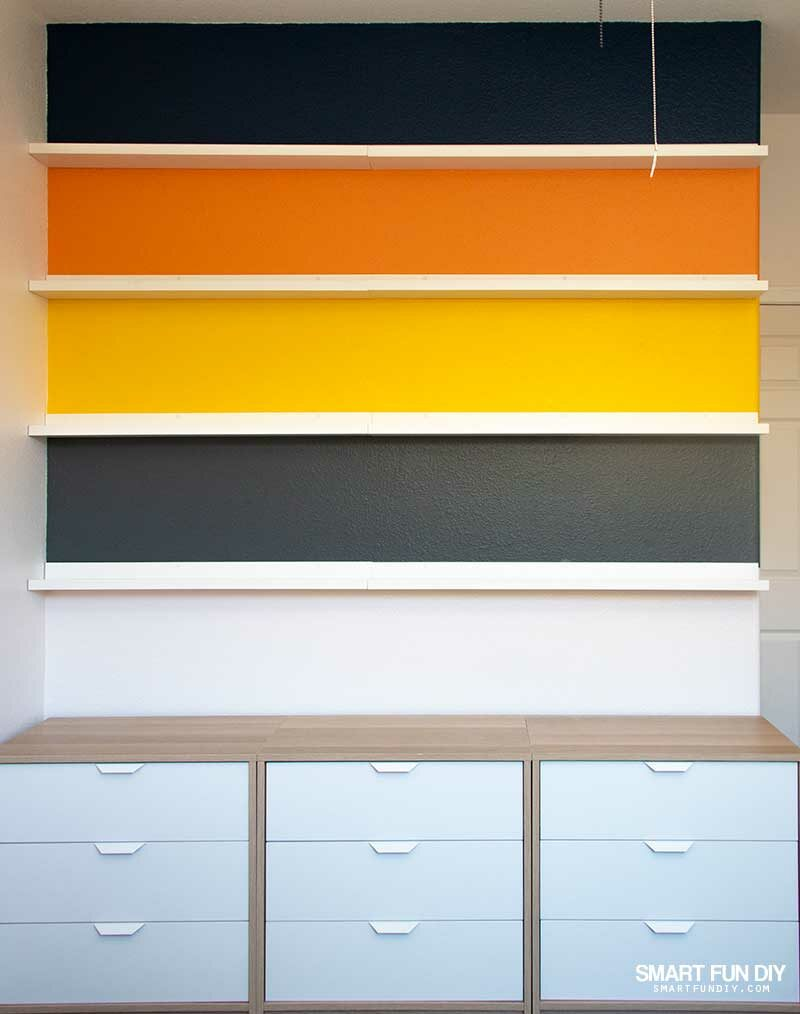 Painted stripes on walls with frame shelves between each stripe and dressers across bottom on floor